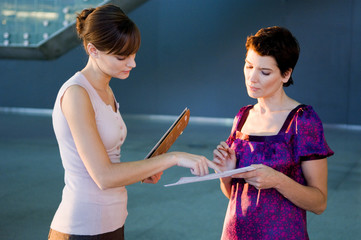Side profile of two interior designers discussion on a blueprint