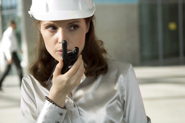 Close-up of a young woman talking on a walkie-talkie