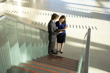 High angle view of a businessman and a businesswoman looking at a diary