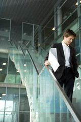 Businessman standing on a staircase with a blueprint