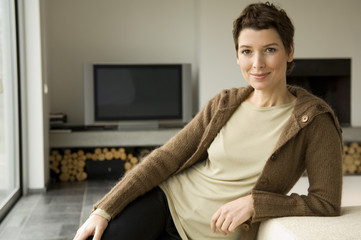 Portrait of a mid adult woman leaning against a couch