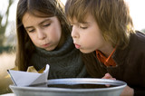 Close-up of two children blowing the paper boat on a bowl of water
