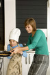 Young woman preparing a pancake with her son