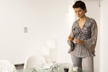 Mid adult woman lighting a candle with a cigarette lighter at a dining table