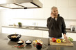 Portrait of a mature man talking on a mobile phone in the kitchen