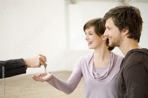 Gros plan sur main d'un agent immobilier tendant clés à un couple