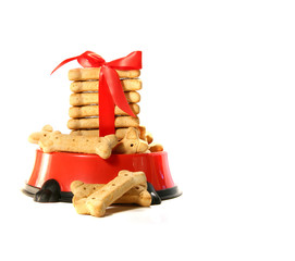 Dog biscuits in bowl with red bow