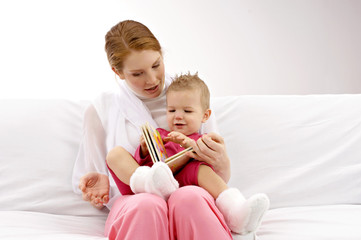 Young woman showing a picture book to her son