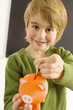 Boy putting a coin into a piggy bank