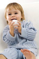 Close-up of a baby boy sitting on a couch and playing with a toy