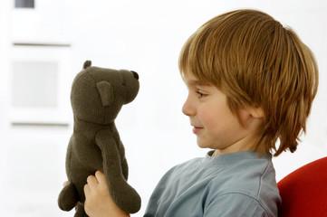 Side profile of a boy holding a teddy bear