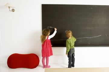 Two children drawing on a blackboard