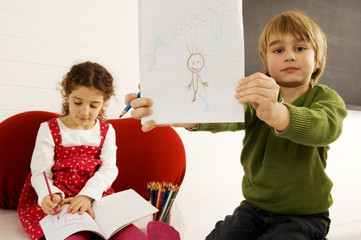 Portrait of a boy showing a drawing with his sister sitting in the background