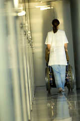 Rear view of a female doctor pushing a patient sitting in a wheelchair