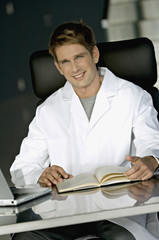 Portrait of a male doctor sitting at a desk in his office