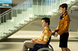 Side profile of a female cabin crew pushing a mid adult man sitting in a wheelchair