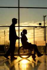 Silhouette of a man pushing a female patient sitting in a wheelchair