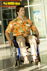 Mid adult man sitting in a wheelchair at an airport