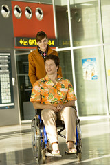 Female cabin crew pushing a mid adult man sitting in a wheelchair