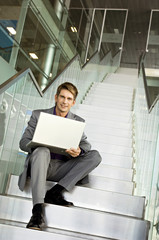 Portrait of a businessman sitting on a staircase and using a laptop