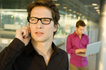 Close-up of a businessman talking on a mobile phone with another businessman using a laptop in the background