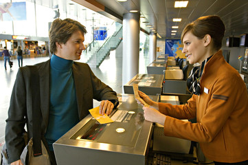 Businessman with a female check-in attendant at an airport check-in counter