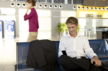 Businessman using a mobile phone at an airport lounge