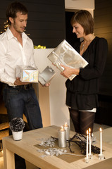 Mid adult man and a young woman holding Christmas presents