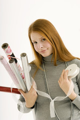 Portrait of a young woman holding rolls of wrapping papers