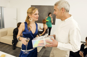 Mature man giving a gift to a young woman in a party