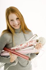 Portrait of a young woman holding rolls of wrapping papers and smiling