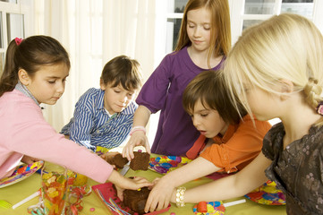 Children picking up pieces of a cake