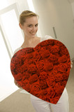 Young woman holding a heart shape gift and smiling