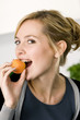 Portrait of a young woman eating an apricot