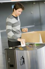 Mid adult man putting garbage into a garbage bin
