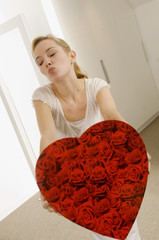 Young woman holding a heart shape gift and puckering her lips