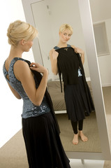 Young woman trying on a dress in front of a mirror