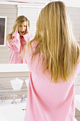 Reflection of a young woman looking in mirror and shouting