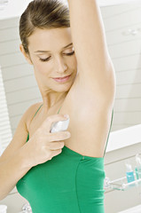 Side profile of a young woman applying deodorant on her underarm