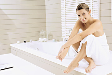 Portrait of a young woman sitting on a bathtub and smiling