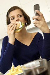 Close-up of a young woman eating a burger and looking at a mobile phone