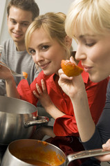 Young woman tasting tomato sauce with a ladle with a young man and a young woman beside her in the kitchen