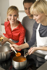 Two young women and a young man preparing food in the kitchen