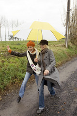 Two young women sheltering under an umbrella and walking on a dirt road
