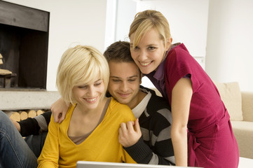 Two young women with a young man in front of a laptop