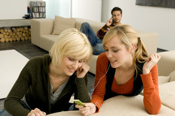 Two young women listening to an MP3 player