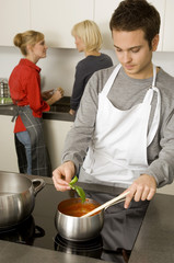Young man preparing food with two young women talking with each other in the background