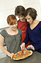 Young woman standing with her friends and cutting a pizza with a pizza cutter