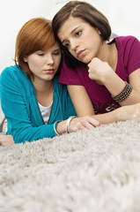 Close-up of two young women lying on a carpet and looking serious