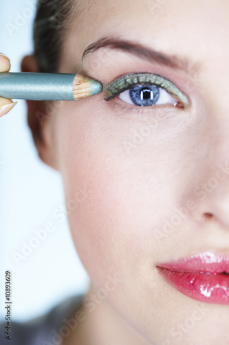 Young woman applying eyeliner